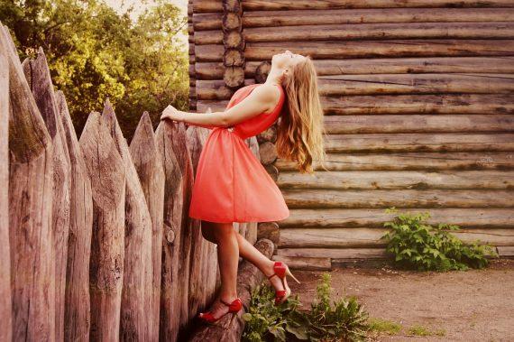 Kobieta w pięknej sukience przy płocie