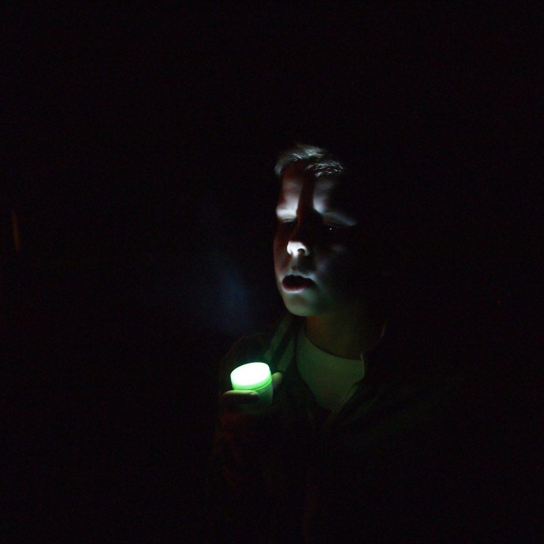 Chłopiec z zieloną latarką w nocy