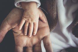 Dłoń dziecka w dłoni mężczyzny