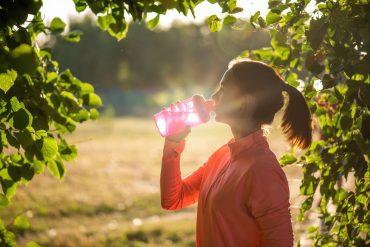 Dziewczyna pije wodę z butelki filtrującej