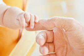 Niemowlę trzyma palec rodzica