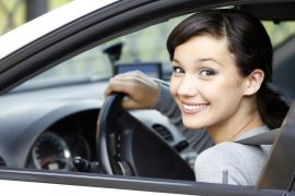 Uśmiechnięta kobieta w wynajętym samochodzie