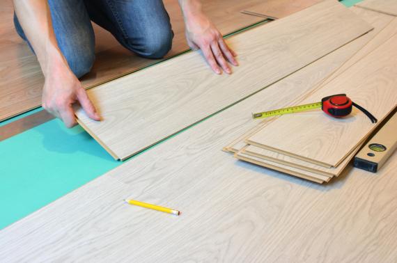 Mężczyzna montuje panele podłogowe