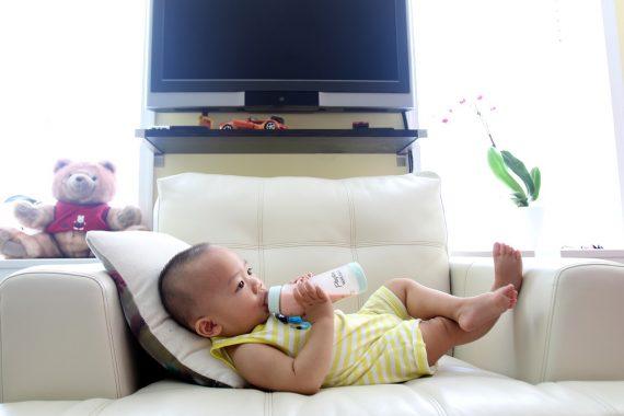 Dziecko pijące mleko z plastikowej butelki