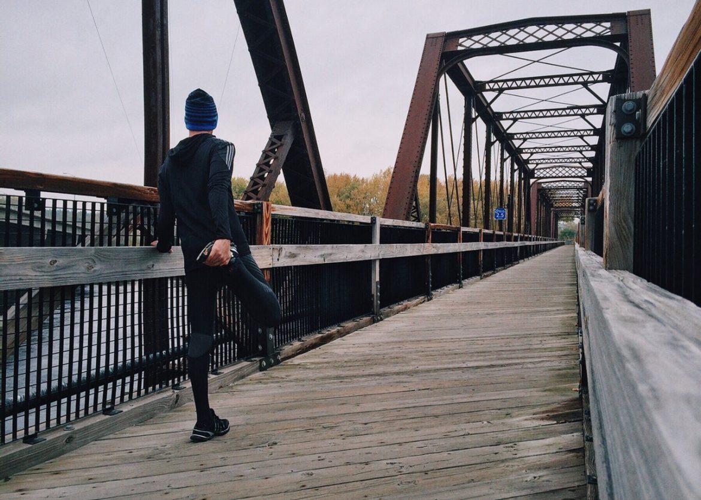 Mężczyzna rozciągający się podczas treningu na drewnianym moście