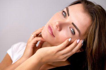 Młoda kobieta dotykająca twarzy w zamyśleniu