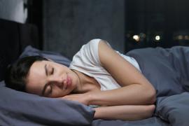 Kobieta śpiąca w szarej pościeli