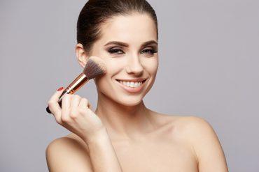 Uśmiechnięta kobieta z pędzlem do makijażu
