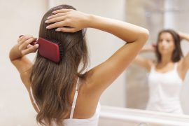 Kobieta przed lustrem czesząca włosy szczotką
