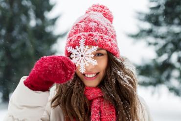 Kobieta w czerwonej czapce, szaliku i rękawiczkach na tle zimowego krajobrazu i z płatkiem śniegu przy twarzy