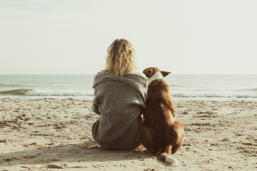 kobieta blondynka z psem na plaży
