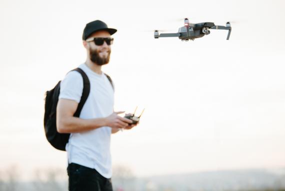 Mężczyzna pilotujący niewielkiego drona