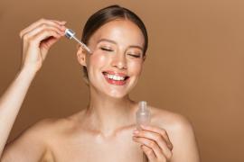 uśmiechnięta kobieta z aplikatorem oleju naturalnego przy twarzy