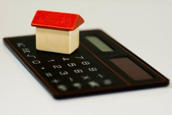 drewniany model domu na kalkulatorze