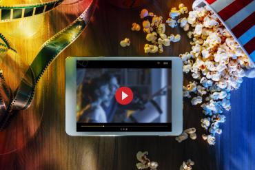 film na tablecie obok popcorn i taśma filmowa