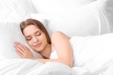 kobieta śpiąca wygodnie w białej pościeli