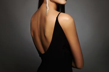kobieta w czarnej seksownej sukience bez pleców z efektownymi kolczykami