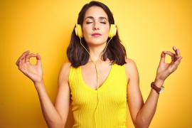 Piękna kobieta w żółtym swetrze z żółtymi słuchawkami na uszach słucha muzyki i relaksuje się