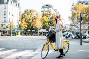 młoda elegancka kobieta na żółtym rowerze na ulicach Paryża