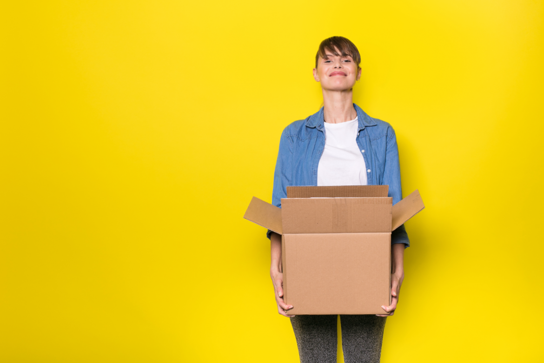 dziewczyna z kartonowym pudłem na żółtym tle