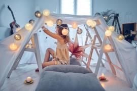 dziewczynka w szarym namiocie z lampkami