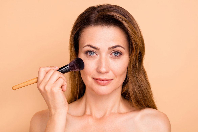 kobieta wykonująca makijaż z pędzlem przy twarzy