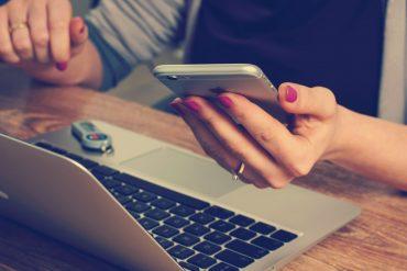 kobieta z różowymi paznokciami trzymająca smartfona w dłoni