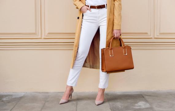 kobieta z torebką w dłoni, w pasku i w skórzanych butach