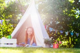dziewczynka w namiocie w ogrodzie