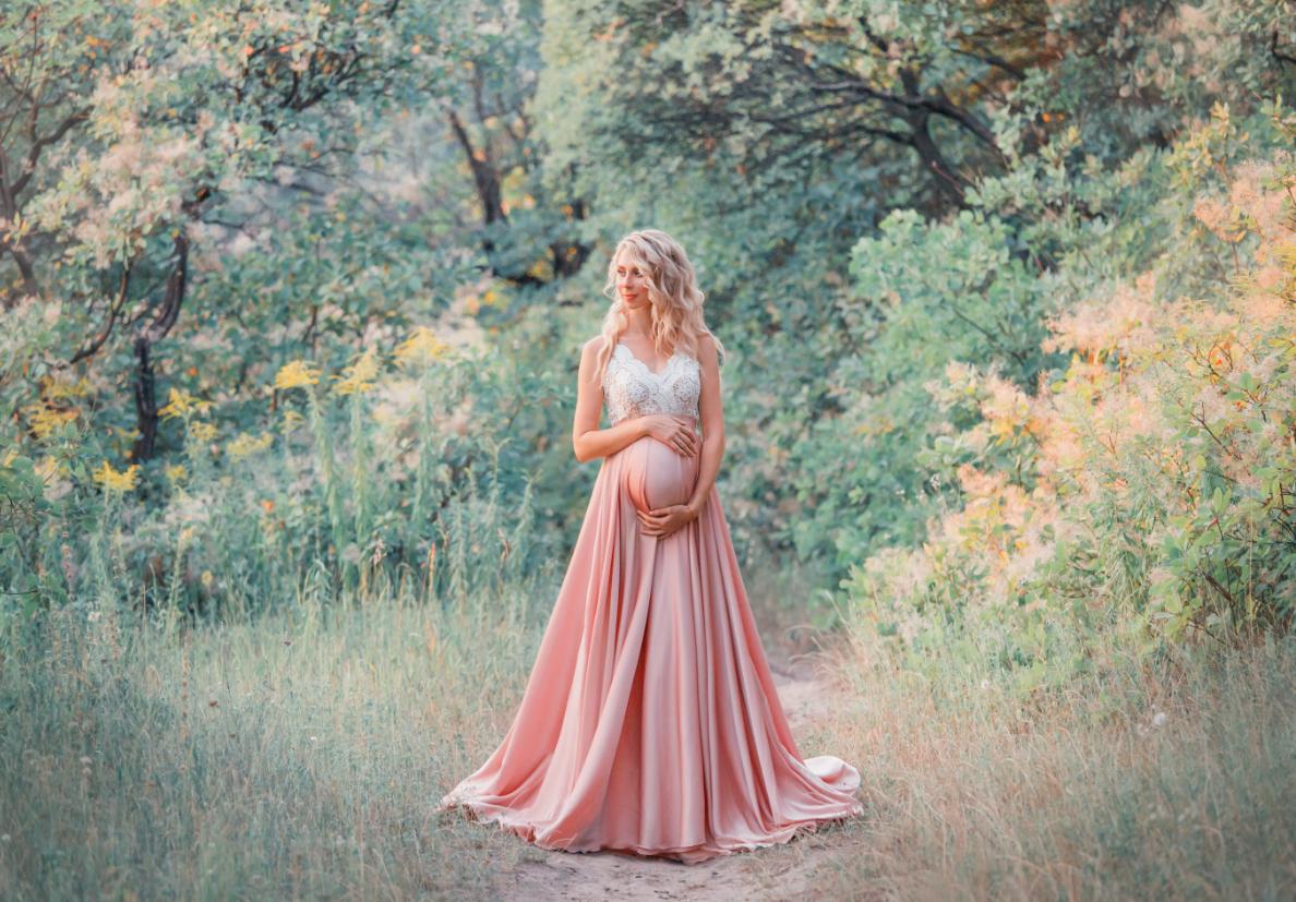 sesja ciążowa kobieta w eleganckiej sukni na tle natury