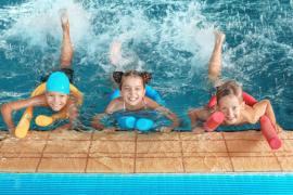 dzieci w basenie uczące się pływać