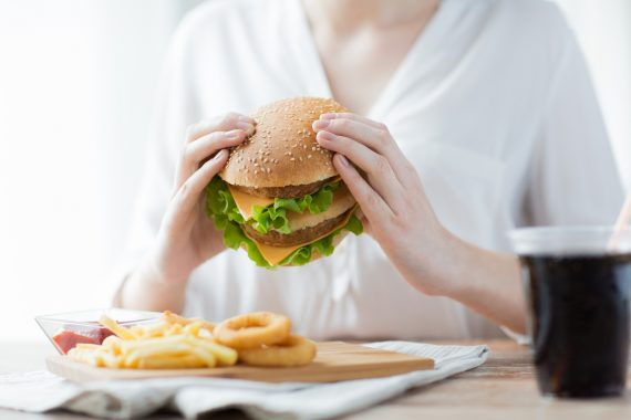 kobieta jedząca hamburgera