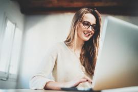 młoda kobieta pisząca list motywacyjny na laptopie