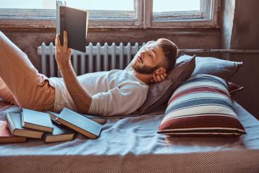 mężczyzna czytający ksiązkę w starym domu