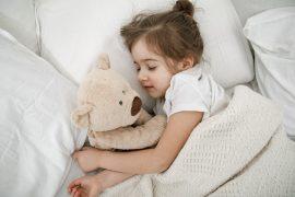 urocza dziewczynka śpiąca z misiem