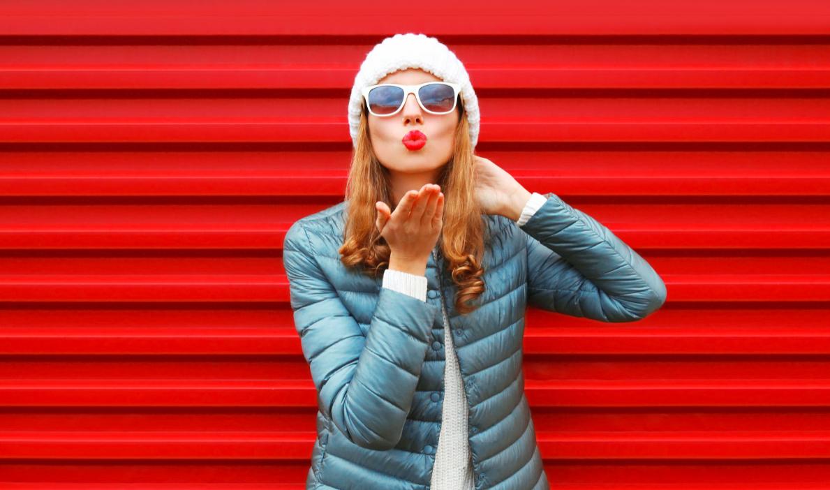 kobieta w kurtce zimowej na czerwonym tle