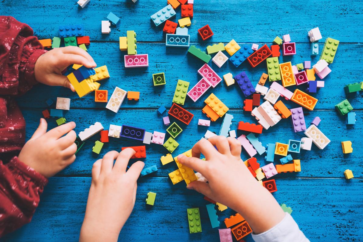 dziecięce dłonie budujące klocki lego