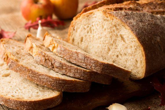 Pokrojony świeży chleb w kompozycji z jesiennymi liśćmi i czosnkiem.
