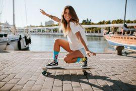 kobieta w kolorowych skarpetkach na deskorolce