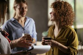 kobiety z kubkami kawy rozmawiające w biurze