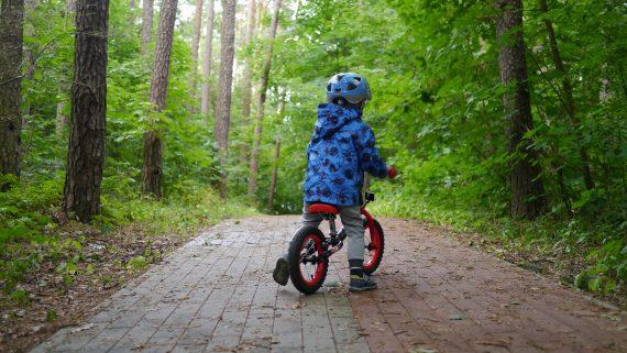 Dziecko w kasku jedzie na rowerze na drodze w lesie wśród drzew.