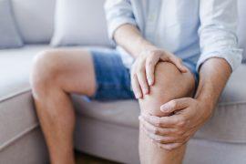 mężczyzna trzymający się za kolano